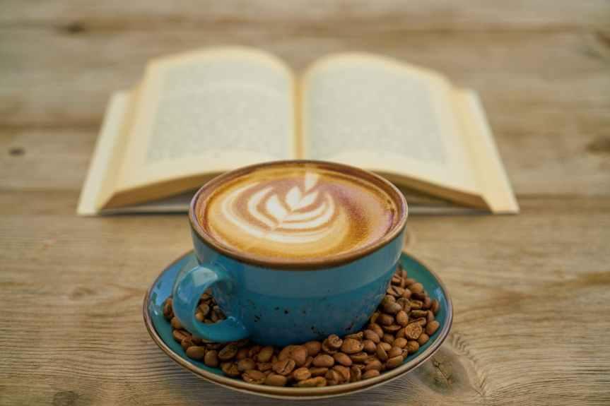 blue ceramic teacup with saucer beside book